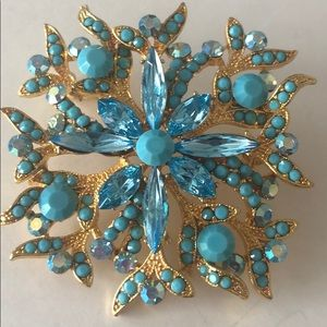 Large gold tone jeweled brooch